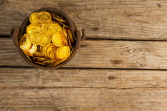 St. Patricks Day pot filled with chocolate gold coins. On wooden background Stock Photos