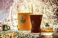 St Patricks Day Pub Alcohol. Saint Patrick`s Day pub items, including a large mug of beer, a glass of Irish stout, and a shot of Irish Whiskey neat. Set against Stock Image