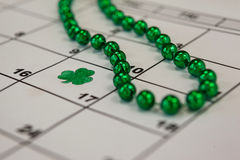 St. Patricks Day shamrock and beads kept on calendar Stock Photos