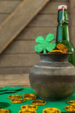 St. Patricks Day shamrock, beer bottle and pot filled with chocolate gold coins Royalty Free Stock Photos