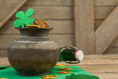 St. Patricks Day shamrock, beer bottle and pot filled with chocolate gold coins Stock Photography