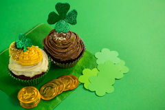 St Patricks Day shamrock on the cupcake with gold coins. On green background Stock Photo