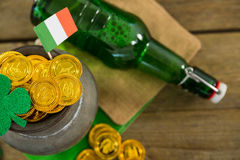 St. Patricks Day shamrock, flag, beer bottle and pot filled with chocolate gold coins Stock Photos