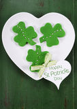St Patricks Day shamrock green cookies. Happy St Patricks Day shamrock shape green fondant cookies on white heart shape plate on vintage style green wood table Royalty Free Stock Photos