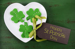 St Patricks Day shamrock green cookies. Happy St Patricks Day shamrock shape green fondant cookies on white heart shape plate on vintage style green wood table Stock Photos