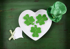 St Patricks Day shamrock green cookies. Happy St Patricks Day shamrock shape green fondant cookies on white heart shape plate on vintage style green wood table Royalty Free Stock Images