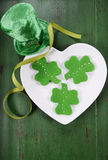 St Patricks Day shamrock green fondant cookies. Happy St Patricks Day shamrock shape green fondant cookies on white heart shape plate on vintage style green wood Royalty Free Stock Photos