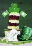 St Patricks Day shamrock green triple cupcake with greeting tag. Happy St Patricks Day triple layer cupcake with shamrock decorations and leprechaun hat against Royalty Free Stock Photography