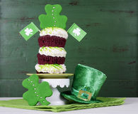 St Patricks Day shamrock green triple cupcake. Happy St Patricks Day triple layer cupcake with shamrock decorations and leprechaun hat against a vintage style Stock Images