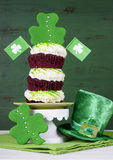 St Patricks Day shamrock green triple cupcake. Happy St Patricks Day triple layer cupcake with shamrock decorations and leprechaun hat against a vintage style Royalty Free Stock Photos