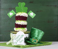 St Patricks Day shamrock green triple cupcake. Happy St Patricks Day triple layer cupcake with shamrock decorations and leprechaun hat against a vintage style Stock Photography