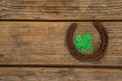 St Patricks Day shamrock with horseshoe. On wooden surface Stock Images