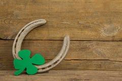 St Patricks Day shamrock with horseshoe. On wooden surface Royalty Free Stock Images