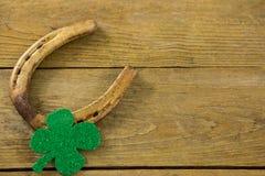 St Patricks Day shamrock with horseshoe. On wooden surface Stock Photography