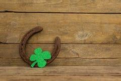 St Patricks Day shamrock with horseshoe. On wooden surface Stock Photo