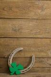 St Patricks Day shamrock with horseshoe. On wooden surface Royalty Free Stock Photography