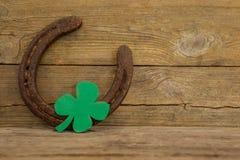 St Patricks Day shamrock with horseshoe. On wooden surface Stock Image
