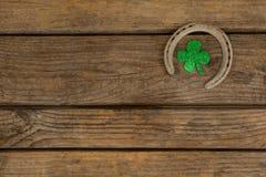 St Patricks Day shamrock with horseshoe. On wooden table Royalty Free Stock Photo