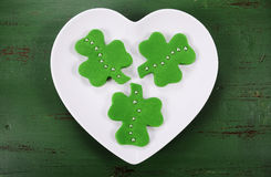 St Patricks Day shamrock shape green fondant cookies. Happy St Patricks Day shamrock shape green fondant cookies on white heart shape plate on vintage style Royalty Free Stock Photography