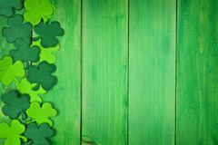 St Patricks Day shamrock side border over green wood. St Patricks Day side border of paper shamrocks over a green wood background stock image