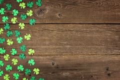 St Patricks Day shamrocks side border over rustic wood. St Patricks Day side border of paper shamrocks over an old rustic wood background Stock Photo