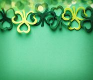 St Patricks Day side border of decoration shamrocks over a green background. Copy space royalty free stock images
