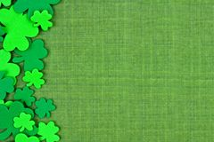St Patricks Day side border of shamrocks over green linen Royalty Free Stock Photos