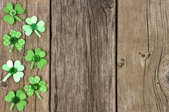 St Patricks Day side border of shamrocks over rustic wood Stock Photo
