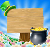 St Patricks Day Sign. A St Patrick's Day concept; pot of gold and a green Leprechaun hat with clover hanging on a wooden sign in a field of flowers Stock Photography