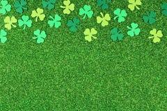 St Patricks Day top border of shamrocks over glittery green background. St Patricks Day top border of shamrocks over a shiny green glitter background