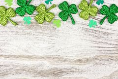 St Patricks Day top border of shamrocks over rustic white wood. St Patricks Day top border of shiny shamrocks over a rustic white wood background royalty free stock photos