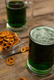 St Patricks Day two mugs of green beer with pretzel Stock Photos