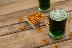 St Patricks Day two mugs of green beer with pretzel Stock Photo