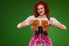 St Patricks Day. Young Oktober fest waitress, wearing a traditional Bavarian dress, serving big beer mugs on green. Half-length portrait of young redhead woman royalty free stock photography