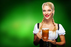 St Patricks Day. Young Oktoberfest waitress, wearing a traditional Bavarian dress, serving big beer mugs on blue Royalty Free Stock Photo