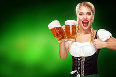 St Patricks Day. Young sexy Oktoberfest waitress, wearing a traditional Bavarian dress, serving big beer mugs on blue Stock Photo