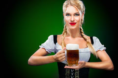 St Patricks Day. Young sexy Oktoberfest waitress, wearing a traditional Bavarian dress, serving big beer mugs on blue Royalty Free Stock Photo