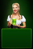 St Patricks Day. Young sexy Oktoberfest waitress, wearing a traditional Bavarian dress, serving big beer mugs on blue. Half-length portrait of young sexy blonde Royalty Free Stock Photo
