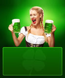 St Patricks Day. Young sexy Oktoberfest waitress, wearing a traditional Bavarian dress, serving big beer mugs on blue. Half-length portrait of young sexy blonde Stock Image