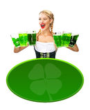 St Patricks Day. Young sexy Oktoberfest waitress, wearing a traditional Bavarian dress, serving big beer mugs on blue. Portrait of young sexy blonde with big Stock Image