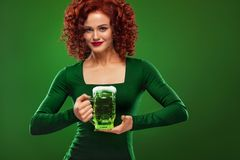St Patricks Day. Young sexy and redhead Octoberfest waitress, wearing a dress, serving big beer mugs on green background. Half-length portrait of young sexy Royalty Free Stock Images