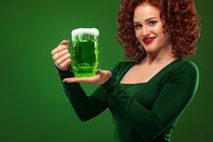 St Patricks Day. Young sexy and redhead Octoberfest waitress, wearing a dress, serving big beer mugs on green background. Half-length portrait of young sexy Stock Photos
