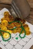 St Patricks dnia czekoladowe złociste monety i koraliki utrzymujący na kalendarzu Zdjęcia Stock