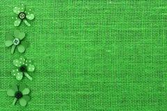 St Patricks dnia granica papierowi shamrocks na zielonym burlap Zdjęcia Royalty Free