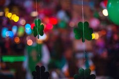 St. Patrick's Day celebrations. St. Patricks& x27;s Day clover decoration in a pub. Bokeh defocused lights in background Royalty Free Stock Photo