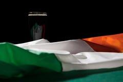 St- Patricktag mit einem halben Liter des schwarzen Bieres und der irischen Flagge über einem g stockfotografie