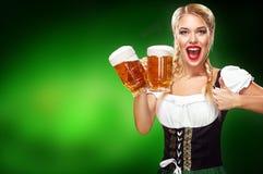 st pattys дня граници Молодая сексуальная официантка Oktoberfest, носящ традиционное баварское платье, служа большие кружки пива  Стоковое Фото