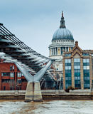 St. Paul Cathedral and the Millenium Bridge. A Thames view of St. Paul Cathedral and the Millenium Bridge in London Royalty Free Stock Images