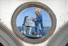 St. Paul healing a sick man, Ospedale di San Paolo in Florence. St. Paul healing a sick man. Glazed terracotta tondo by Andrea della Robbia, located between two royalty free stock image