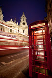 St Paul's cathedral facade, bus and phone box. A bus speeding past the front of St Paul's cathedral in London with a telephone box in the foreground Royalty Free Stock Image